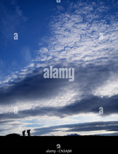 Two people hiking, silhouette - Stock Image