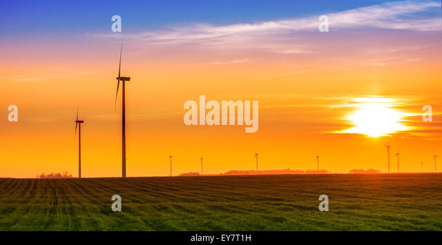 Renewable energy concept, windmills at sunset. - Stock Image