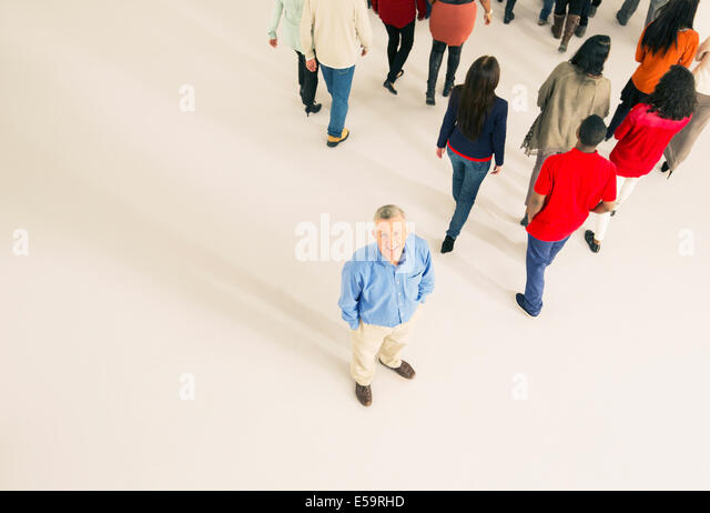 Crowd walking away from man - Stock Image