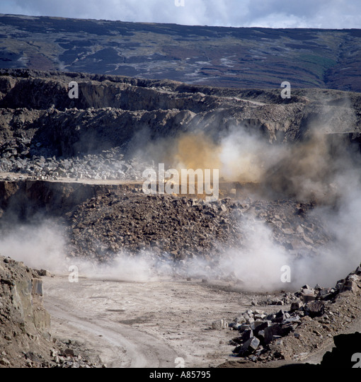 Seconds after blasting a quarry face; Buckton Vale sandstone quarry, Stalybridge, Greater Manchester, England, UK. - Stock Image