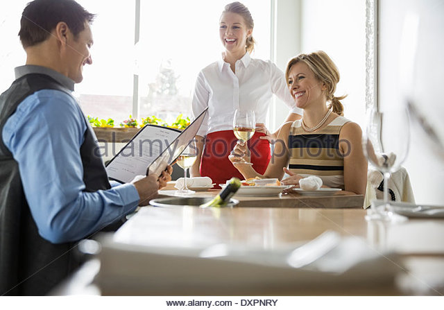 Waitress taking couples order at table in bistro - Stock Image