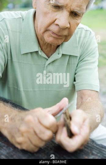 Senior man whittling piece of bark, close-up - Stock Image
