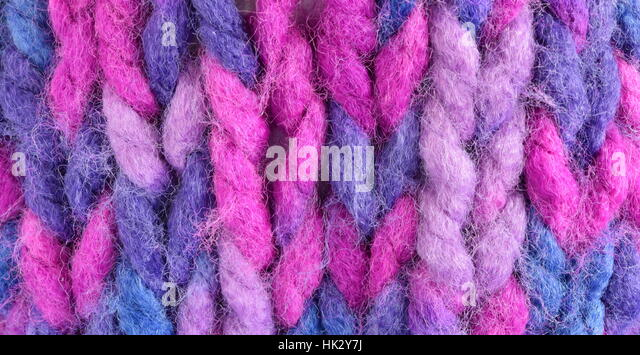 Close-up of a sample of knitting stitch in purple, blue and pink knitting yarn - Stock Image