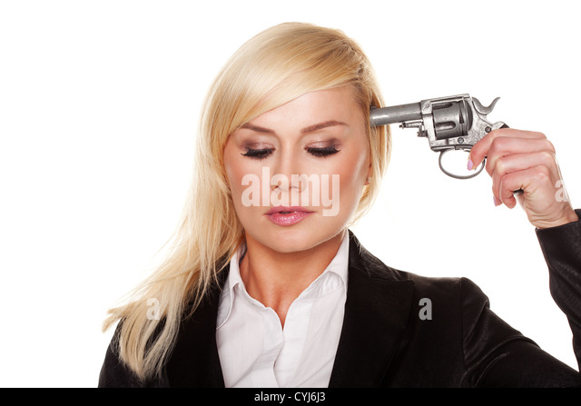 Young professional woman with downcast eyes holding a gun to her head in an attempted suicide or in a demonstration - Stock Image