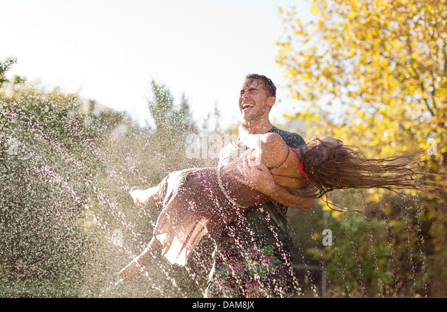 Couple playing in sprinkler in backyard - Stock-Bilder