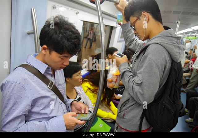Beijing China Subway public transportation passengers riders Asian man woman Airport Express Train Line T3 cabin - Stock Image