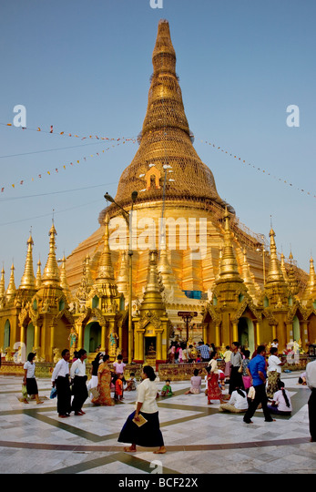 Myanmar, Burma, Yangon. Devout Buddhists at the small stupas, temples, shrines at Shwedagon Golden Temple. - Stock-Bilder