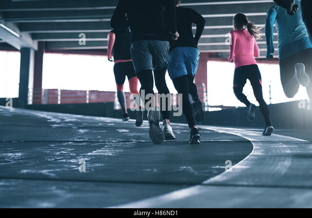 Rear view of unrecognizable sportsmen running in parking place. Copyspace - Stock Image