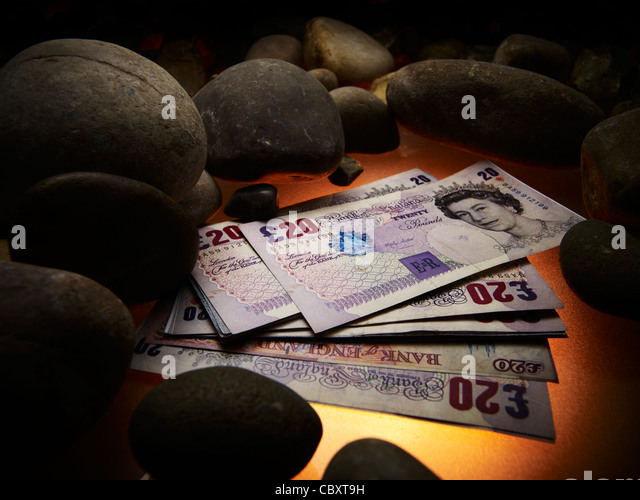 Twenty pound notes next to stones - Stock Image