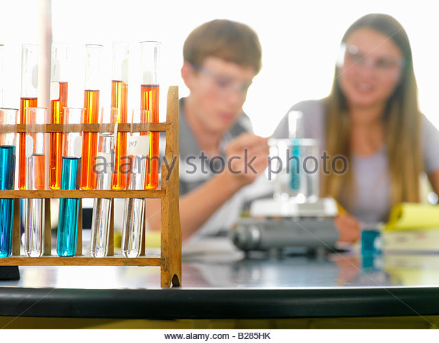 Students (12-14) with chemistry experiment, focus on beakers - Stock Image