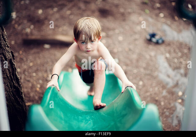 Boy climbing up a slide - Stock Image