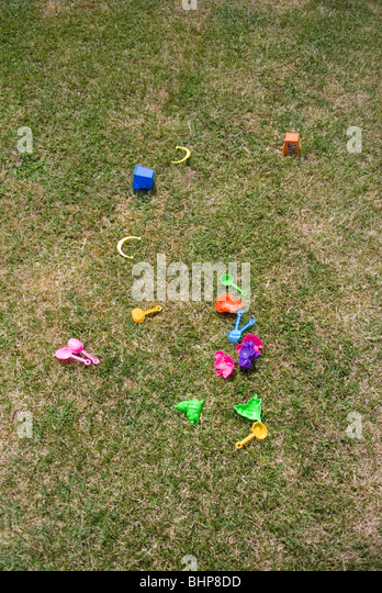 an assortment of brightly coloured kids plastic toys lie scattered on a grass lawn in a private garden - Stock Image