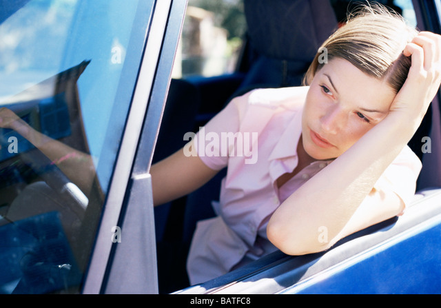 Frustrated driver leaning out of acar window. - Stock Image