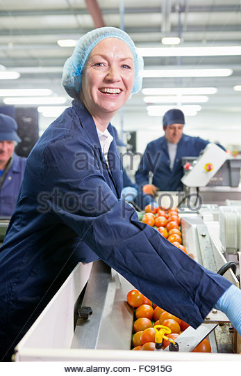 Portrait smiling quality control worker checking tomatoes at production line in food processing plant - Stock Image