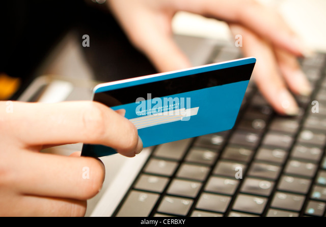 Hands entering credit card information into a laptop - Stock Image