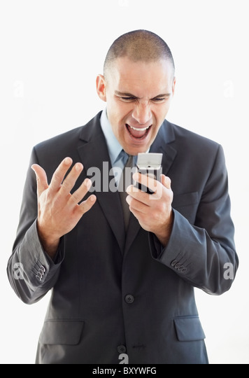 Angry businessman shouting at mobile phone - Stock Image