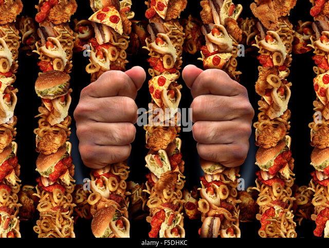 Junk food addiction and eating unhealthy lifestyle concept with aprison bars shaped made of  fried chicken hamburgers - Stock Image