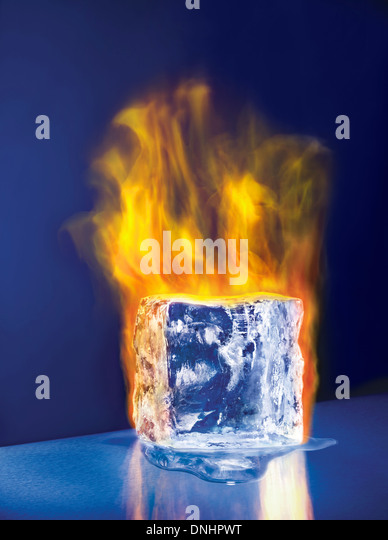 A large melting ice block cube on fire. - Stock Image