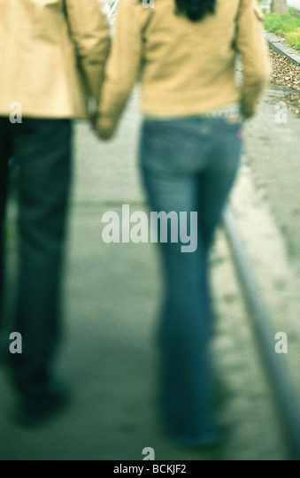 Couple walking holding hands on sidewalk, lower section - Stock-Bilder