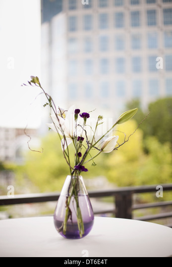 A table on a terrace in the city. A vase of flowers. Small purple flowers, and white lily and orchid blooms. - Stock Image