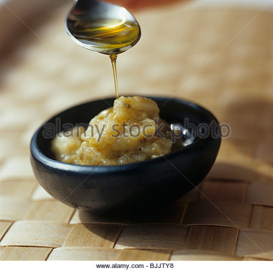 Pouring oil onto aubergine dip - Stock Image