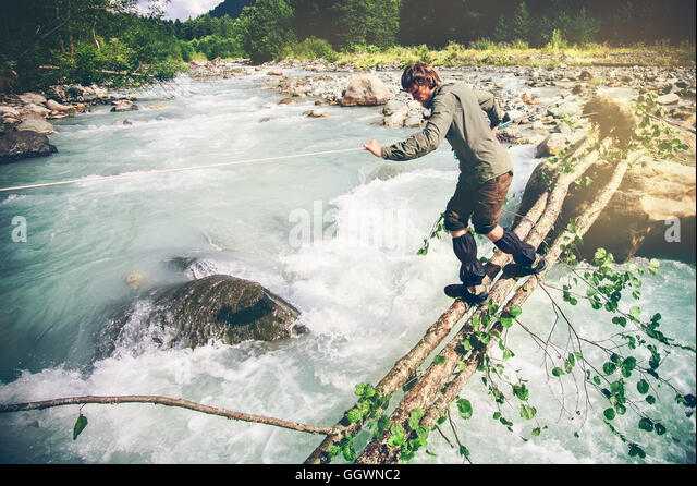 Man Traveler crossing over river on woods outdoor Lifestyle Travel extreme survival concept - Stock Image