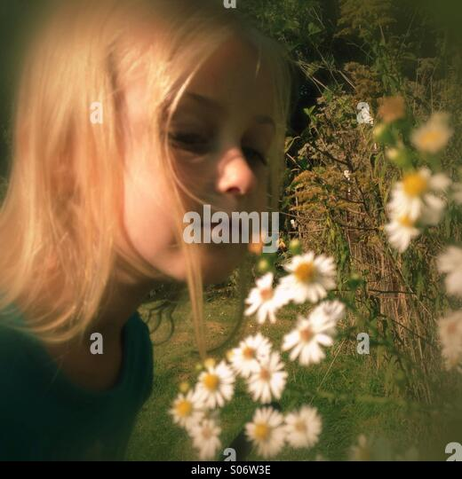 A child taking time to smell the flowers. - Stock Image