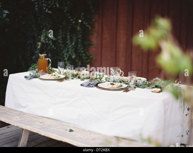 A table laid for a special meal Place settings with plates and cutlery Glasses A white table cloth and bench seat - Stock Image