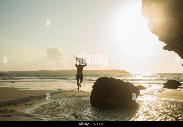 Mature man running towards sea, holding surf board - Stock Image