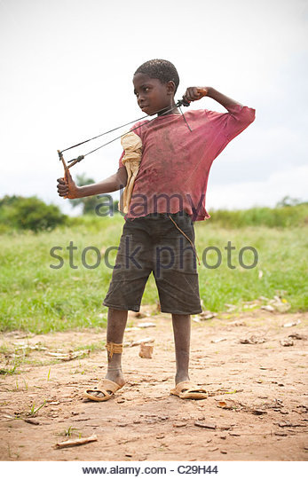 A young Congolese boy with his slingshot on the Congo River shoreline. - Stock-Bilder