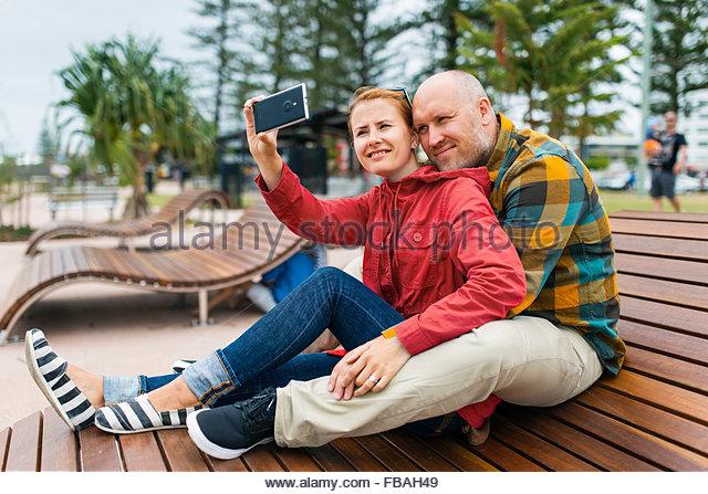 Australia, Queensland, Mid-adult couple taking selfie on bench in park - Stock Image