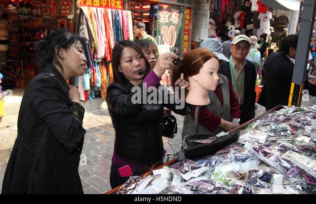 A woman combs a mannequin wig at a galanterie, talks on a microphone and shows a potential client a hair clip. Cibao - Stock Image