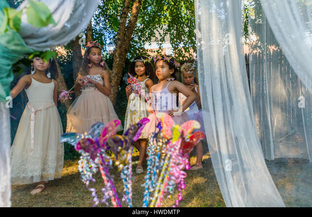 Group of young girls dressed as fairies, playing outdoors - Stock-Bilder