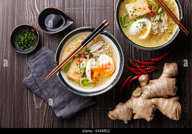 Asian Miso ramen noodles with egg, tofu and enoki in bowls on gray wooden background - Stock Image