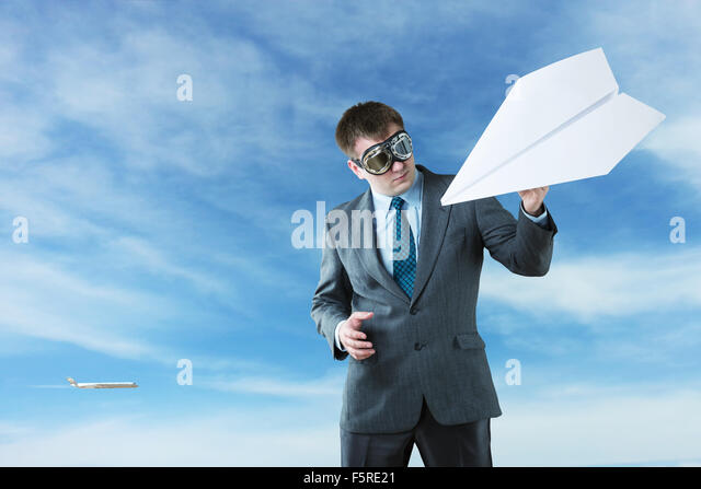 Businessman with paper plane and wearing goggles isolated on sky background - Stock Image