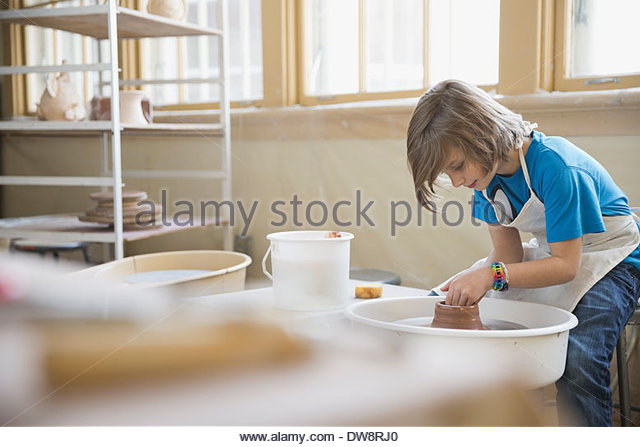 Boy working on clay in pottery class - Stock Image