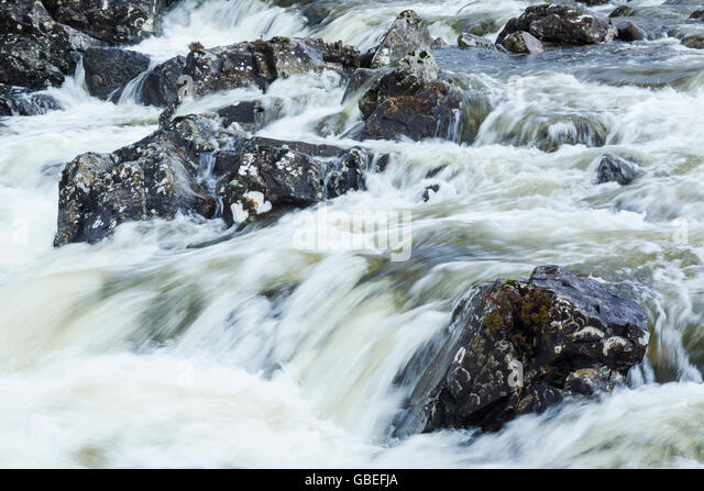 Energetic and aggressive river flowing between boulders - Stock Image