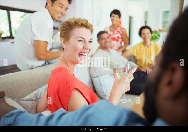 Friends laughing together at party - Stock Image