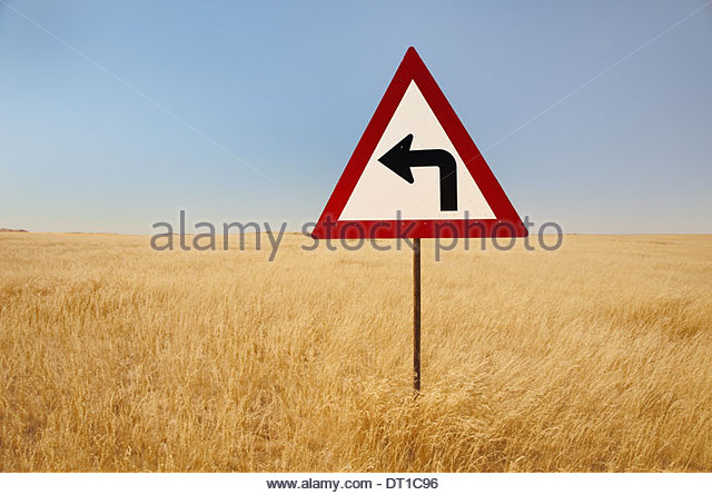 Namibia turn left traffic sign middle tall grasses Namibia - Stock Image