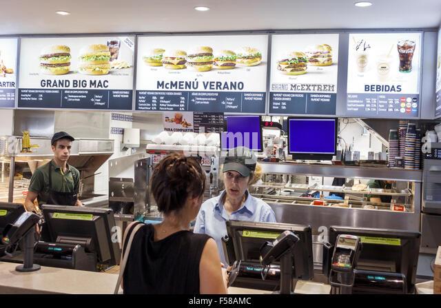 Toledo Spain Europe Spanish Plaza de Zocodover McDonalds fast food restaurant hamburger menu cashier counter customer - Stock Image