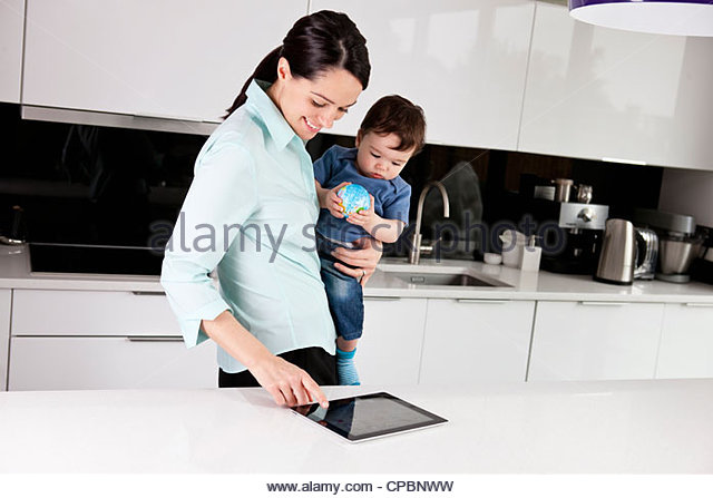 A mother and her baby son looking at a digital tablet, baby holding a globe ball - Stock-Bilder