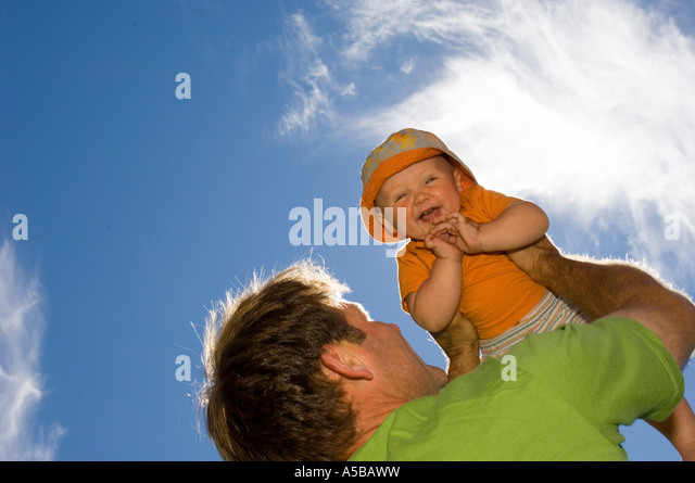 Father holding baby up into the sky. - Stock Image