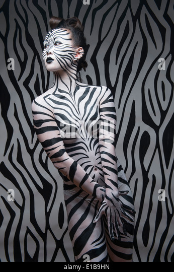 A woman with her body painted in black and white zebra stripes to match the background - Stock Image