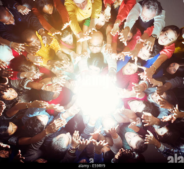 Diverse crowd reaching for bright light - Stock Image