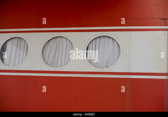 part of an airplane fuselage with three portholes - Stock Image
