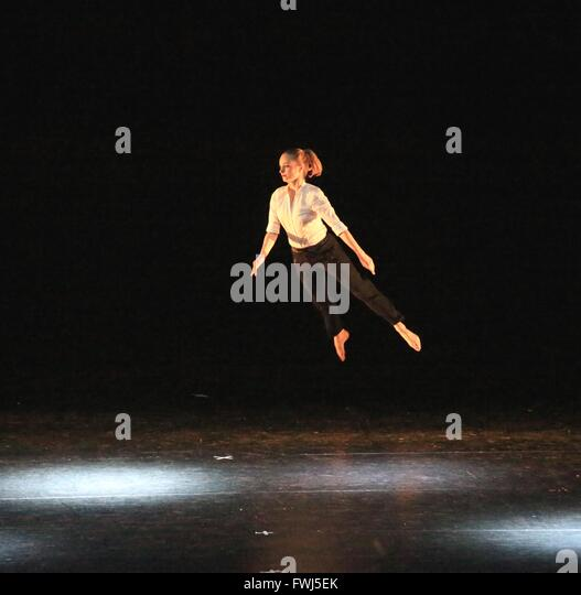 Full Length Of Young Woman Standing Mid Air Against Black Background - Stock-Bilder