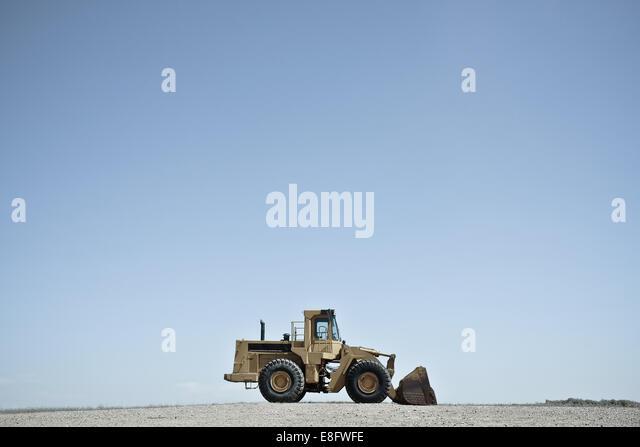 USA, Wyoming, Bulldozer against blue sky - Stock-Bilder