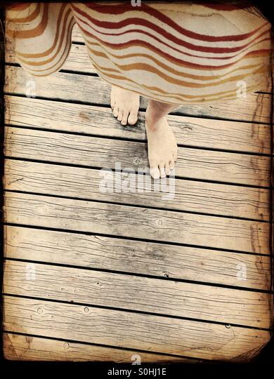 A woman walking a wooden pier - Stock Image
