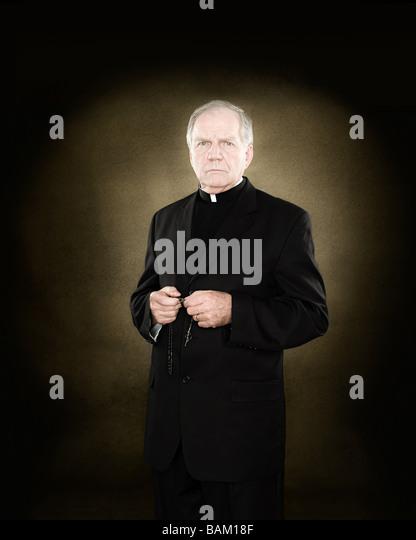 A priest holding prayer beads - Stock Image