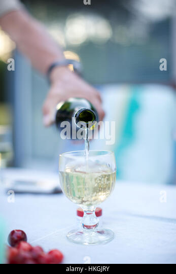 white wine being poured into glass. alcohol, beverage, party, refreshment. - Stock-Bilder